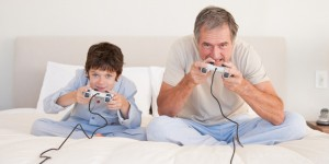 a grandfather playing video games with his grandson in bed